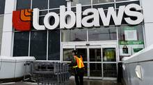A Loblaws employee brings in shopping carts in Toronto on Wednesday, Feb. 18, 2009. (NATHAN DENETTE/NATHAN DENETTE/The Canadian Press)
