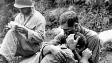 An American infantryman, his buddy killed in action in the Korean War, weeps on the shoulder of another GI somewhere in Korea, in this Aug. 28, 1950 file photo. (AP/Al Chang)