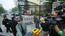 "Chinese policemen close the gate to the apartment compound where jailed dissident Liu Xiaobo home is located, in Beijing on October 8, 2010. China said that the Norwegian Nobel committee has ""violated"" the integrity of the Peace Prize by awarding it to jailed dissident Liu Xiaobo and warned that ties with Oslo would suffer. (GOH CHAI HIN/GOH CHAI HIN/AFP/Getty Images)"