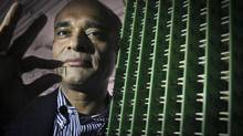 Aereo founder and CEO Chet Kanojia stands next to a server array of antennas as he holds an antenna between his fingers. (Bebeto Matthews/AP)