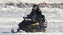 Canada's Prime Minister Stephen Harper rides a snowmobile with members of the Canadian Rangers on Frobisher Bay in Iqaluit, Nunavut February 23, 2012. (CHRIS WATTIE/REUTERS)