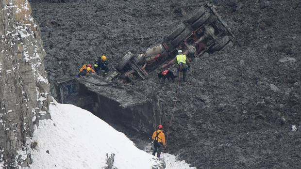 Rescue workers, along with a dog, check out a buried vehicle at a quarry in L'Epiphanie, Que., just east of Montreal, on Jan. 29, 2013. A dramatic rescue operation is underway following an apparent landslide at the quarry, with two workers missing. (Graham Hughes/THE CANADIAN PRESS)