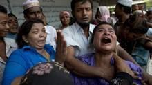 A woman of a mosque fire victim cries during the burial of her son on the outskirts of Yangon, April 2, 2013. (Gemunu Amarasinghe/AP)
