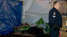 A police officer stands near a tent where a woman died at the Occupy Vancouver site in downtown in Vancouver, B.C., on Saturday November 5, 2011. (Darryl Dyck/ The Canadian Press/Darryl Dyck/ The Canadian Press)