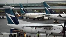 WestJet aircraft are pictured at the gates at Toronto Pearson Airport on May 26, 2016. (Fred Lum/The Globe and Mail)