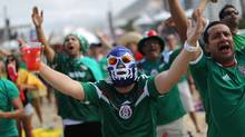 Soccer fans, one wearing a Lucha Libre wrestling mask, react as they watch the World Cup match between Mexico and Cameroon on a screen inside the FIFA Fan Fest area on Copacabana beach in Rio de Janeiro, Brazil, Friday, June 13, 2014. Mexico overcame the torrential rain and two disallowed goals to beat Cameroon 1-0 on Friday, picking up the three points it needed to have any chance of advancing from a tough group at the World Cup. (Leo Correa/(AP Photo/Leo Correa))