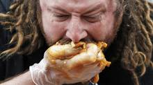 'Crazy Legs' Conti scarfs down a handful of fries, gravy and cheese curds at the World Poutine Eating Competition in Toronto on Saturday. (Mark Blinch/Reuters/Mark Blinch/Reuters)