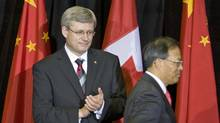 Prime Minister Stephen Harper applauds as Chinese Ambassador Lan Lijun makes his way to the podium to deliver a speech marking 40 years of diplomatic relations with China at an event in Ottawa on Oct. 13, 2010. (Adrian Wyld/THE CANADIAN PRESS)