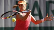 Canada's Eugenie Bouchard returns the ball during the third round match of the French Open tennis tournament against Sweden's Johanna Larsson at the Roland Garros stadium, in Paris, France, Friday, May 30, 2014. (David Vincent/AP)