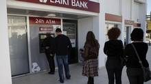 People queue to use an ATM machine outside of a Laiki Bank branch in Larnaca, Cyprus on March 16, 2013. (Petros Karadjias/AP)