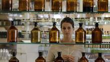 """Caroline De Boutiny, the perfume creator or """"nose"""" at the Galimard perfume factory, holds paper scent testers in her laboratory in Grasse, southeastern France, Nov. 14, 2012. Perfume makers are urging the European Commission to back down from possible legislation they fear could kill top fragrances by restricting natural ingredients linked to allergies. (Eric Gaillard/Reuters)"""