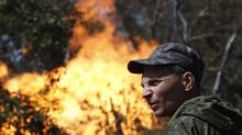 An armed pro-Russian separatist looks as flames erupt from a gas pipeline after shelling in Donetsk on Aug. 15, 2014. (SERGEI KARPUKHIN/REUTERS)