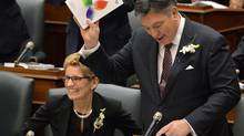 Ontario Finance Minister Charles Sousa, right, delivers the Ontario 2016 budget next to Premier Kathleen Wynne, left, at Queen's Park in Toronto on Thursday, February 25, 2016. THE CANADIAN PRESS/Nathan Denette (Nathan Denette/THE CANADIAN PRESS)