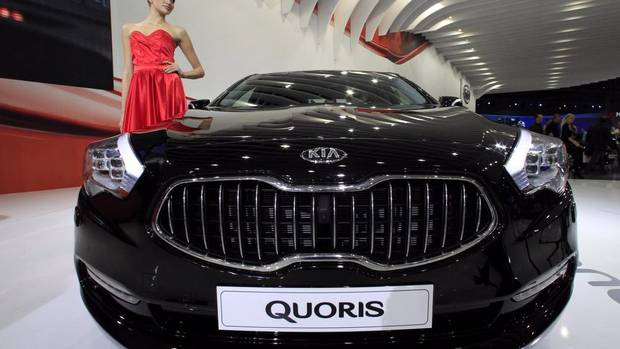 A model stands next to a Kia Quoris during preparations for the Moscow International Automobile Salon Aug. 29, 2012. Russia is one of Europe's few growth markets for auto sales. (SERGEI KARPUKHIN/REUTERS)