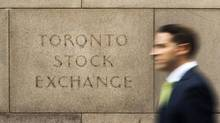 A man walks past an old TSX sign in Toronto. (Mark Blinch/Reuters)
