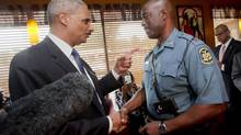 In this Aug. 20, 2014 file photo, Attorney General Eric Holder talks with Capt. Ron Johnson of the Missouri State Highway Patrol at Drake's Place Restaurant in Florrissant, Mo. (Pablo Martinez Monsivais/AP)