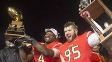 Laval Rouge et Or Pascal Lochard, (4), holds the MVP trophy and teammate Vincent Desloges (95), defensive player of the game, celebrate their victory at the Vanier Cup against the Calgary Dinos Saturday November 23, 2013 in Quebec City. (Clement Allard/THE CANADIAN PRESS)