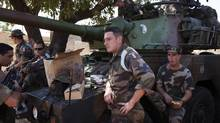 French soldiers stand next to a tank at a Malian air base in Bamako, January 15, 2013. (JOE PENNEY/REUTERS)