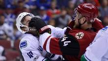 Arizona Coyotes defenseman Kevin Connauton shoves Vancouver Canucks left wing Sven Baertschi during the third period at Gila River Arena. (Matt Kartozian/USA Today Sports)