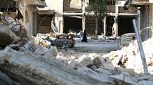 People walk past rubble of damaged buildings in a rebel-held besieged area in Aleppo, Syria November 6, 2016. (ABDALRHMAN ISMAIL/REUTERS)