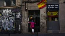 A woman stands next to Spanish flags as she waits to enter a building in central Madrid on June 13, 2012. (SUSANA VERA/REUTERS)