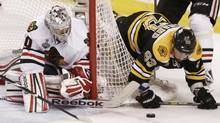 Chicago Blackhawks goalie Corey Crawford (L) and Boston Bruins' Brad Marchand battle for the puck during the second period in Game 6 of their NHL Stanley Cup Finals hockey series in Boston, Massachusetts, June 24, 2013. (WINSLOW TOWNSON/REUTERS)