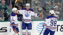 Edmonton Oilers' Andrej Sekera (2) of Slovakia and Jesse Puljujarvi (98) of Sweden celebrate with Connor McDavid after McDavid scored in the third period of an NHL hockey game against the Dallas Stars on Saturday, Nov. 19, 2016, in Dallas. The score was McDavid's third of the game. (Tony Gutierrez/AP)