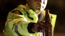RCMP Cnst. Faz Majid removes an open bottle of beer from a motorist's car during a roadside check in Surrey, B.C., on September 24, 2010. (Darryl Dyck/The Canadian Press/Darryl Dyck/The Canadian Press)
