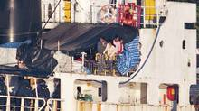 Some of the estimated 490 people thought to be Tamil migrants aboard the ship MV Sun Sea peer out from underneath a tarp after Canadian Border officials and police brought the ship into Canadian Forces Base Esquimalt in Colwood, B.C. on Vancouver Island on Friday. (Andy Clark/Reuters/Andy Clark/Reuters)