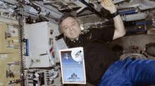 Astronaut Bob Thirsk floats aboard the International Space Station with a copy of Arrows to the Moon, a book by Victoria author Chris Gainor. (Canadian Space Agency)