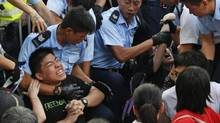 Protesters are taken away by police officers after hundreds of protesters staged a peaceful sit-insearlier this summer in the financial district in Hong Kong. (Kin Cheung/AP)