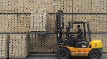 A worker operates a forklift to transport floor boards at a wood flooring factory in Huzhou, Zhejiang province July 13, 2012. (SEAN YONG/REUTERS)