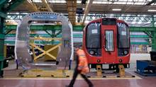 An employee passes components of London Underground tube train carriages at Bombardier's rail-car factory in in Derby, U.K., in 2011. The plant will build overground rail cars for the city's transit authority under a new order worth $137-million (U.S.) (Jason Alden/Bloomberg)