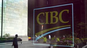 A pedestrian passes in front of CIBC signage displayed outside of the company's office near Bay Street in Toronto on Aug. 29, 2011.