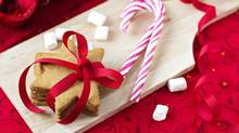 Gingerbread cookies with candy canes on a cutting board (VeselovaElena/Getty Images/iStockphoto)