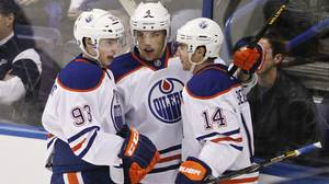 Edmonton Oilers' Ryan Nugent-Hopkins, left, and Taylor Hall, centre, celebrate Jordan Eberle's goal during the first period of their NHL hockey game against the St. Louis Blues in St. Louis, Missouri March 26, 2013.