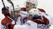 Montreal Canadiens left wing Rene Bourque, centre, celebrates with defenceman Josh Gorges, left, and centre Alex Galchenyuk after Bourque scored against the Florida Panthers during overtime in an NHL game, Thursday, Feb. 14, 2013 in Sunrise, Fla. (Wilfredo Lee/The Associated Press)