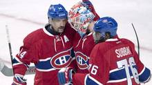 Montreal Canadiens goalie Mike Condon is congratulated by teammates Tomas Plekanec, left, and P.K. Subban, right, after defeating the New Jersey Devils 2-1 in NHL hockey action Wednesday, Jan. 6, 2016 in Montreal. (Ryan Remiorz/THE CANADIAN PRESS)