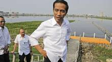 Indonesian presidential candidate Joko Widodo talks to the media during his visit at a reservoir development project in Jakarta on July 22, 2014.