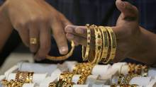 A saleswoman at a store in Bangalore shows off gold jewellery. (Aijaz Rahi)