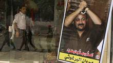 Members of Hamas national security forces are reflected in a souvenir shop window with a poster of jailed Fatah leader Marwan Al-Barghouti as they patrol a street to celebrate a prisoner swap between Hamas and Israel, in Gaza City October 12, 2011. (REUTERS/MOHAMMED SALEM/REUTERS/MOHAMMED SALEM)