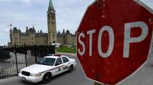 An RCMP cruiser drives past a stop sign on Parliament Hill in Ottawa on Thursday, June 13, 2013. (Sean Kilpatrick/THE CANADIAN PRESS)