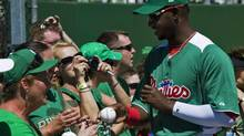 In this file photo Philadelphia Phillies outfielder John Mayberry Jr. (R) signs autographs for fans before a St. Patrick's Day spring training game against the Toronto Blue Jays in Clearwater, Florida, March 17, 2012. (STEVE NESIUS/REUTERS)