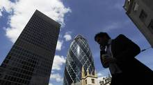 A man passes the Swiss RE building, also known as the Gherkin, in the financial district City of London June 22, 2010. (LUKE MACGREGOR/Reuters/LUKE MACGREGOR/Reuters)