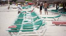 A couple stand near empty beach chairs in Cancun on April 13, 2010. Canada and Mexico are putting new air travel measures in place that should boost tourism and business opportunities between the two countries, Mexico's ambassador says. (GERARDO GARCIA/REUTERS)
