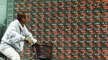 A cyclist checks share prices in Tokyo. (Toshiyuki Aizawa)