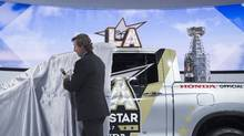 Hockey legend Wayne Gretzky unveils a Honda Ridgeline pickup truck, revealing the Stanley Cup trophy in its bed, that will be given to the MVP player of the 2017 Honda NHL All-Star Game during the four-day auto trade show AutoMobility LA at the Los Angeles Convention Center on November 17, 2016 in Los Angeles, California. (David McNew/Getty Images)