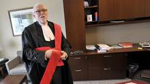 Judge Colin Westman of the Ontario Court of Justice in Kitchener puts on his robe while speaking with the Globe and Mail about his criticisms of the victim surcharge system used in Canada, in judges chambers December 11, 2013. (J.P. MOCZULSKI For The Globe and Mail)