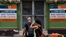 People walk past a vacant building for lease on May 8, 2017 in San Juan, Puerto Rico. The country is struggling under a mountain of debt. (MARK RALSTON/AFP/Getty Images)