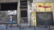A man walks in front of a row of closed shops in central Athens. (John Kolesidis/Reuters)